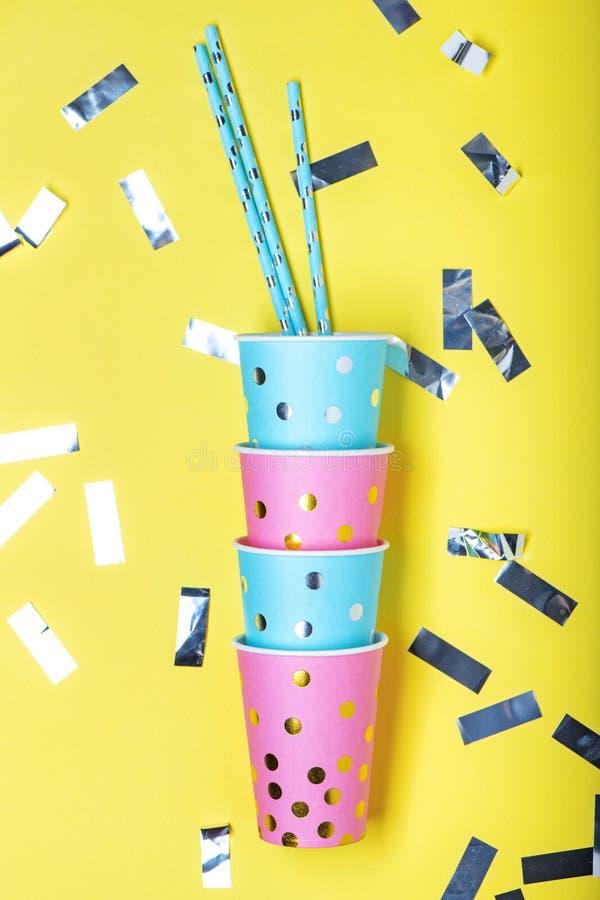 Koppar och sugrör för blå och rosa prick pappers- på gul bakgrund royaltyfri fotografi