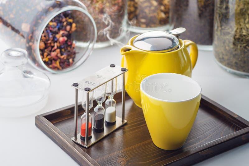 Koppar och tekannan ställde in med klockor och löst te i en behållare på vit bakgrund, produkten för tesalong på träplattan royaltyfri foto