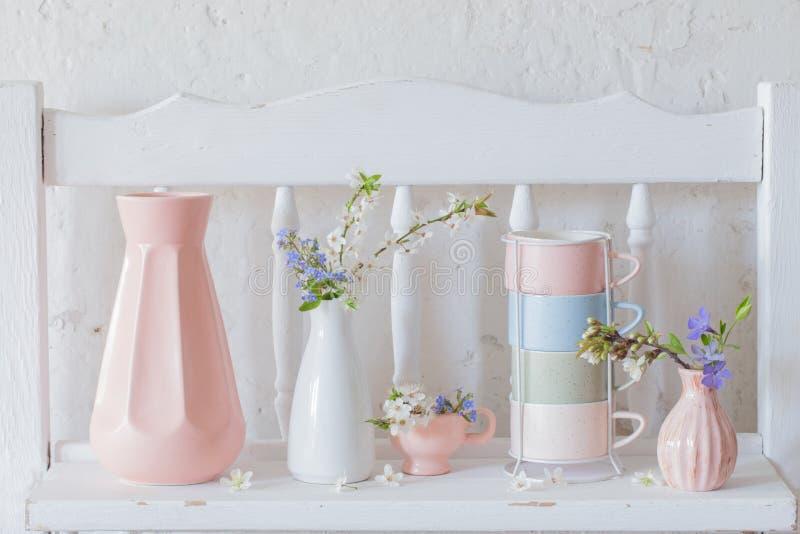 koppar och vaser med v?rblommor p? tr?vit hylla royaltyfria foton