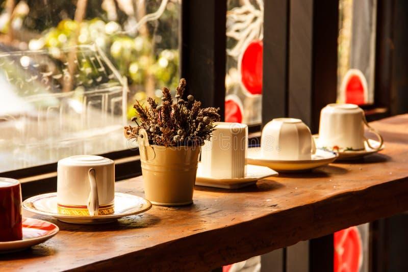 Koppar på hyllan i varmt solljus i romantisk atmosfär av coffee shop arkivbilder