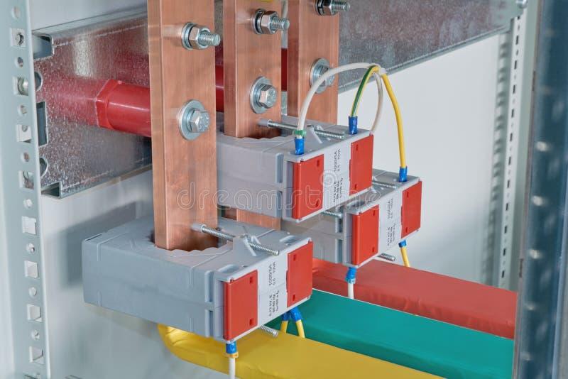 Kopparbusbars med aktuella transformatorer på dem i ett elektriskt kabinett royaltyfria foton
