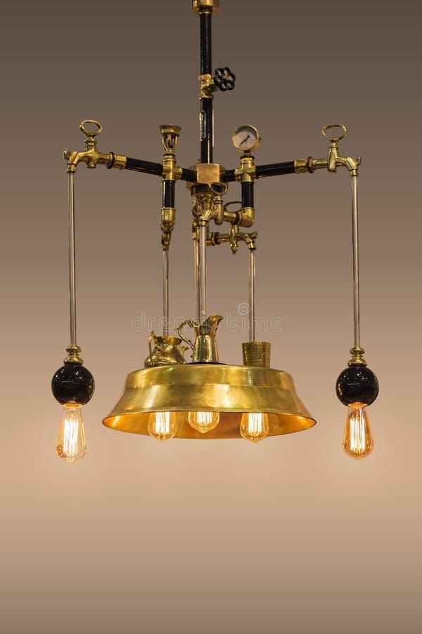 Koppardesignljuskrona, guld- färglampa som är handgjord från brons, i steampunkstil som isoleras arkivfoto