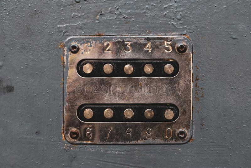 Kopparfärgnummerknappar som låser dörrlåset upp Cupreous panel med nummer på den gamla metalldörren Unlocker knappar på metall royaltyfri fotografi