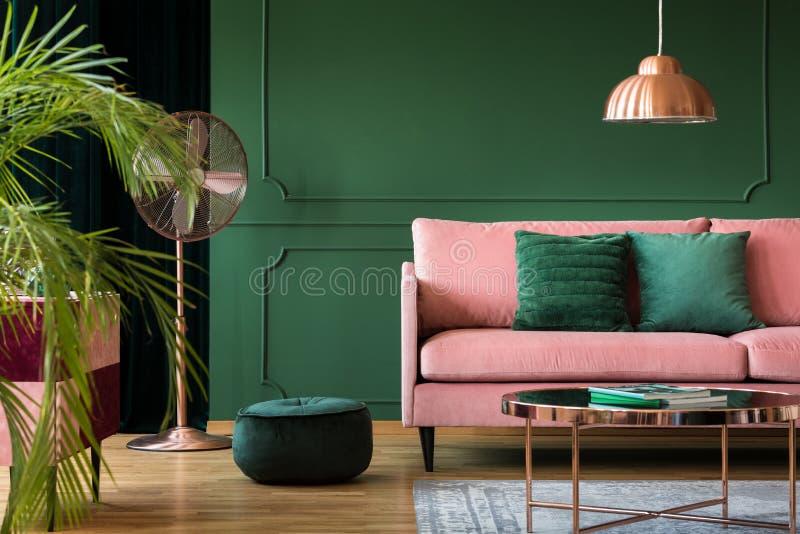 Kopparlampa och tabell i en grön vardagsruminre Verkligt foto royaltyfria bilder
