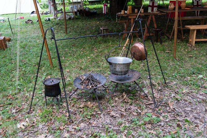 Kopparpanna på brand med soppa under en historisk reena för medeltid arkivbild