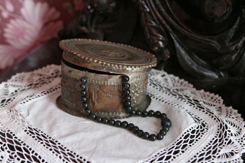 Kopparsmyckenask med svarta pärlor på en stucken servett royaltyfri bild