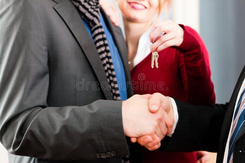Koppel het ontvangen van sleutels van onroerende goederenmakelaar stock afbeeldingen
