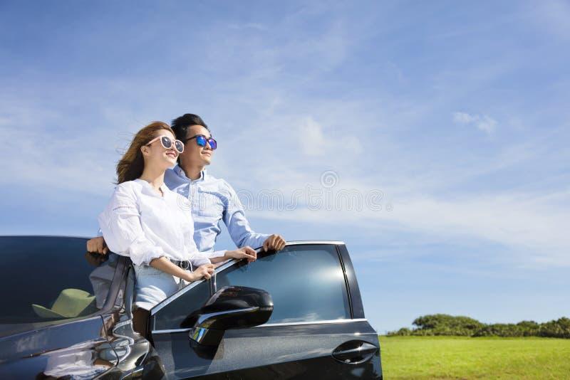 koppel status dichtbij de auto en geniet de zomer van vakantie royalty-vrije stock foto