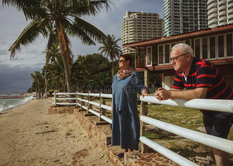Koppelen de bejaarden dichtbij zijn huis op de kust lettend op het het naderbij komen onweer Tropische toevlucht stock foto's