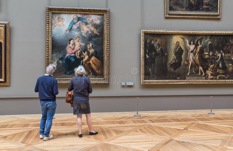 Koppelen de bejaarden het bekijken het schilderen in het Louvremuseum royalty-vrije stock fotografie