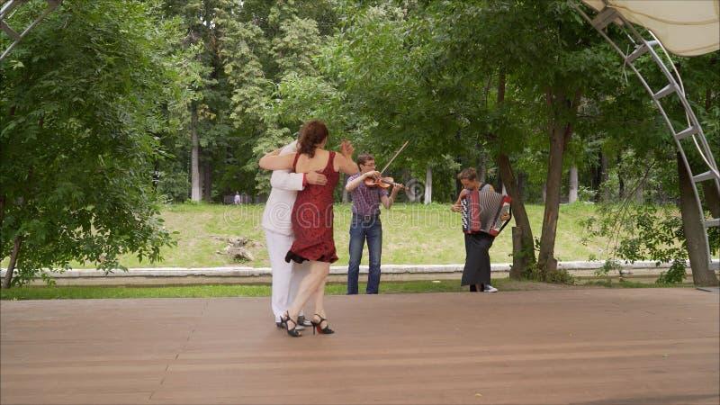 Koppelen de bejaarden het dansen tango in het park royalty-vrije stock afbeeldingen