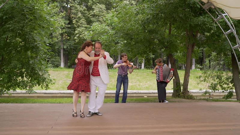 Koppelen de bejaarden het dansen tango in het park stock afbeeldingen