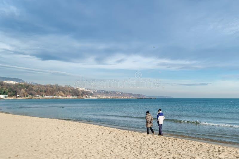 Koppelen de bejaarden het lopen langs het overzeese strand bij de brandingslijn op een warme zonnige de winterdag royalty-vrije stock foto