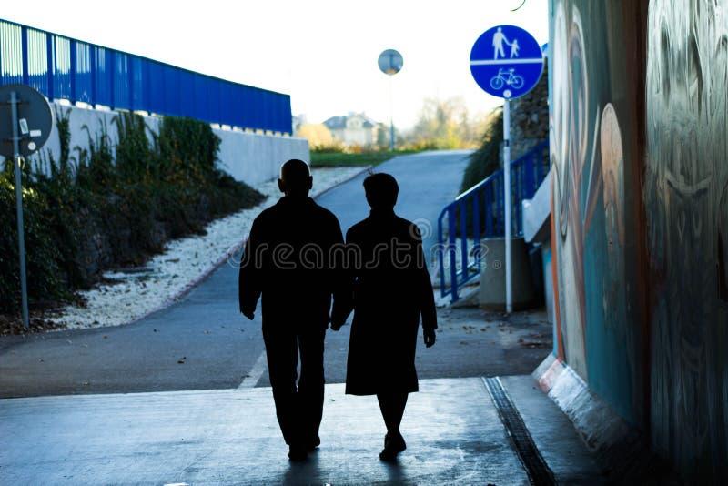 Koppelen de bejaarden holdingshanden op de straat Dit is liefde! royalty-vrije stock afbeelding