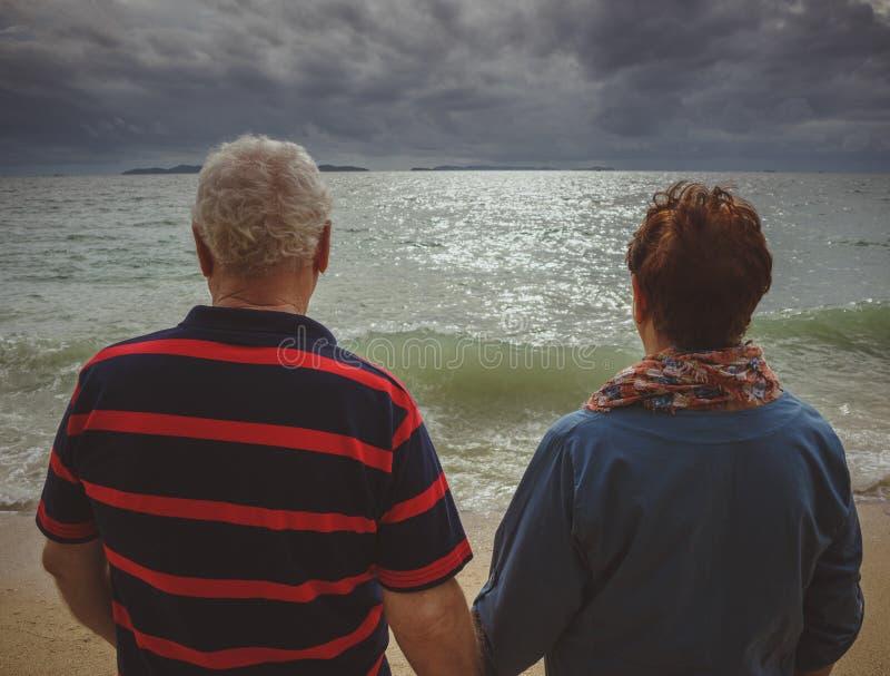 Koppelen de bejaarden holdingshanden, op zee bekijkend het onweer Achtermening, terug naar camera royalty-vrije stock afbeelding