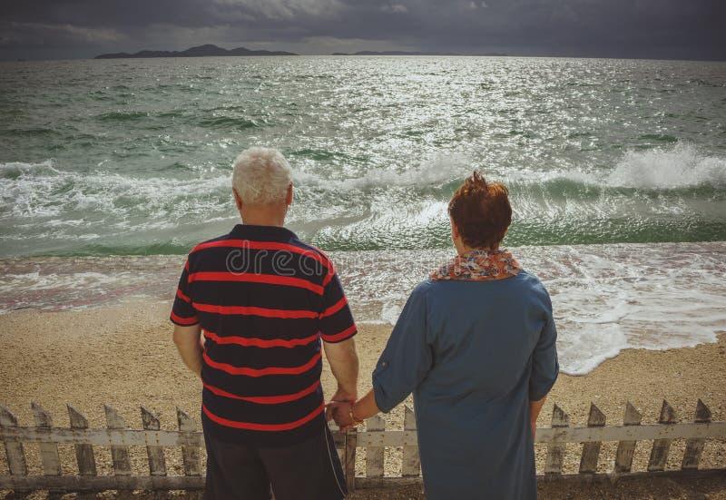 Koppelen de bejaarden holdingshanden, op zee bekijkend het onweer Achtermening, terug naar camera royalty-vrije stock fotografie