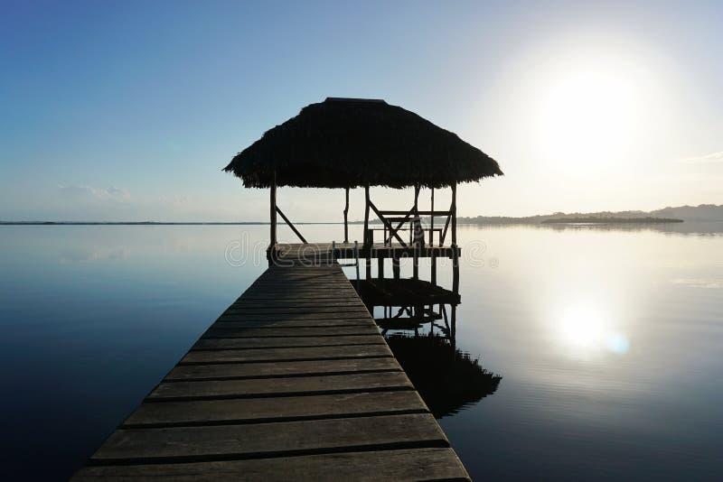 Koppeln Sie mit tropischer Hütte über Wasser auf Sonnenaufganglicht an lizenzfreies stockfoto