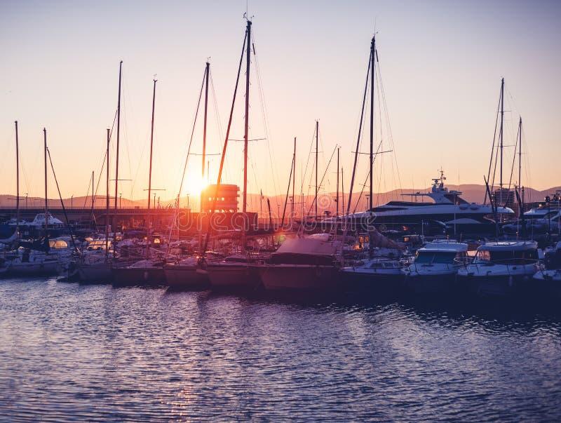 Koppeln Sie mit weißen Booten und Yachten auf einem schönen bunten Sonnenuntergang an stockfotografie