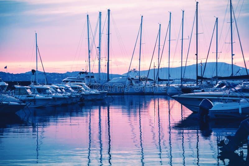 Koppeln Sie mit weißen Booten und Yachten auf einem schönen bunten Sonnenuntergang an stockbilder