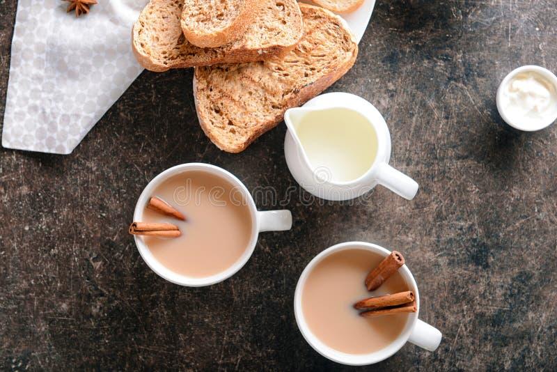 Koppen av aromatiskt te med kanel, mjölkar och nytt bröd på tabellen royaltyfri foto