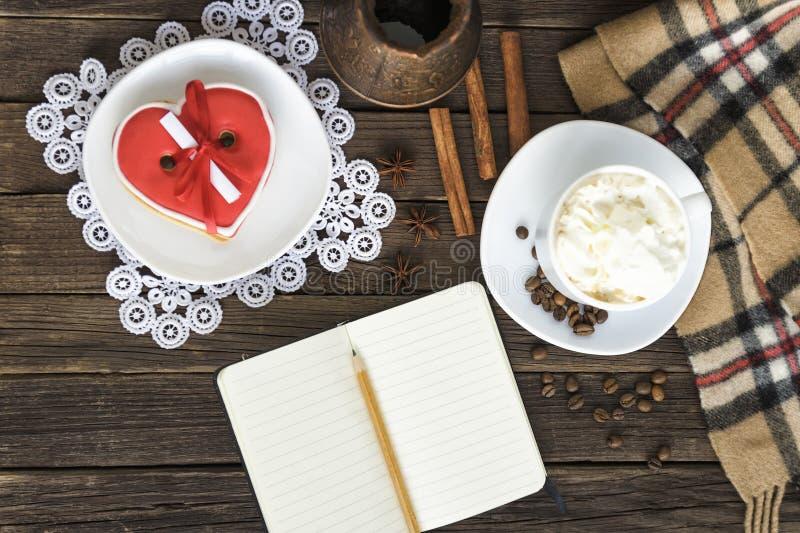 Koppen av cappuccino, hjärta formade krukor för för för den kakabreddmeddelandet, anteckningsboken, blyertspennan och kaffe på en royaltyfri bild
