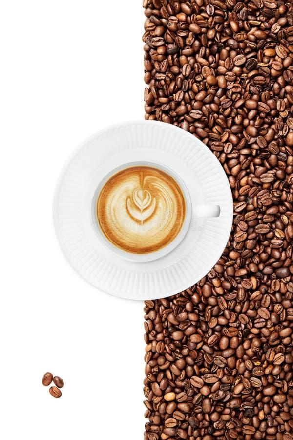 Koppen av ett sent, 3 isolerade kaffebönor i det vänstra nedersta hörnet, kopphandtag vippade på rätt arkivbild