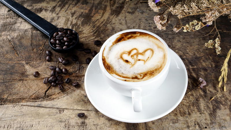 Koppen av lattekaffe med mjölkar pålagt en wood tabell med mörker grillade kaffebönor royaltyfri bild