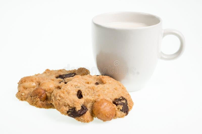 Koppen av mjölkar mjölkar och kakor som isoleras på vit bakgrund arkivfoto