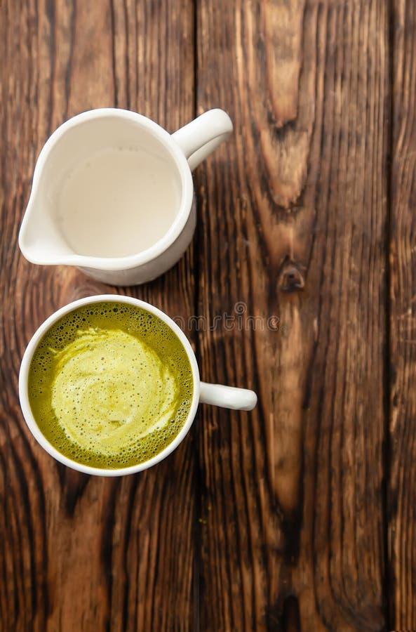 Koppen av varm latte för grönt te för matcha och koppen av mjölkar på träbakgrund royaltyfri fotografi