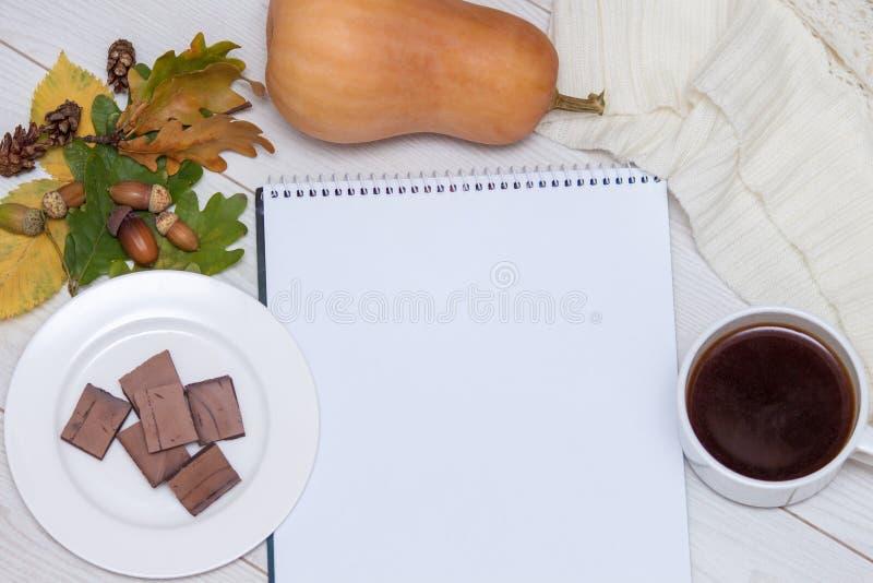 Koppen av varmt kaffe, choklad, höstsidor, ekollonar, stack halsduken, pumpa, anteckningsbok på en träbakgrund Bästa sikt, lägenh arkivfoto
