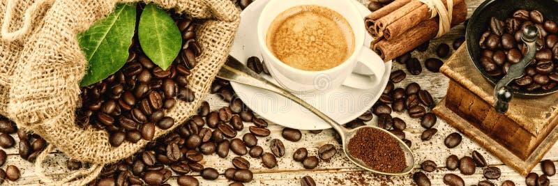 Koppen av varmt svart kaffe med gammalt trä maler molar och säckväv royaltyfri bild