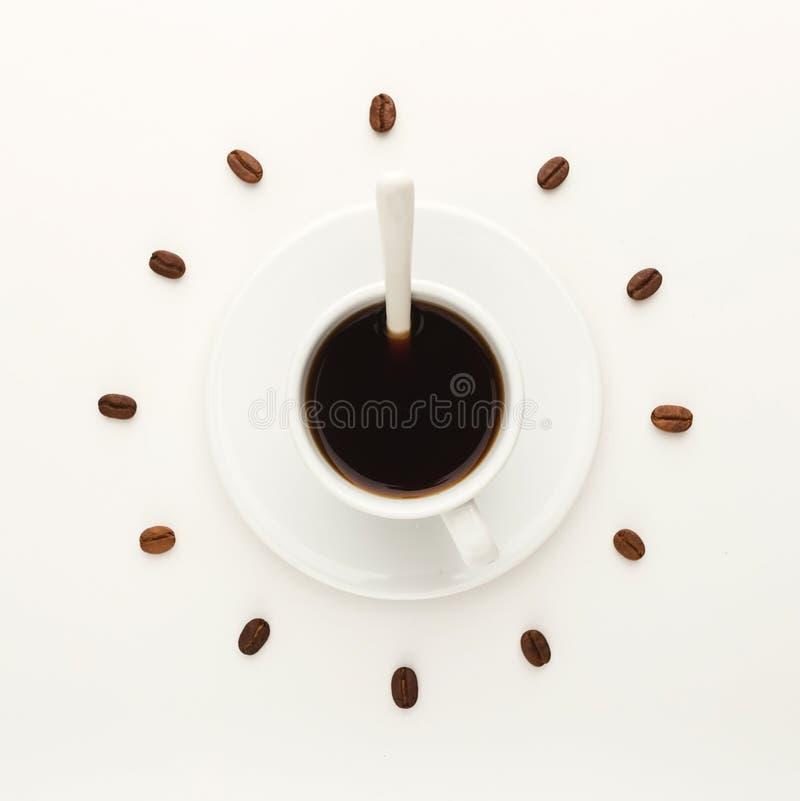 Koppen för svart kaffe och grillade bönor som bildar klockavisartavlan, isolerade nolla royaltyfri foto