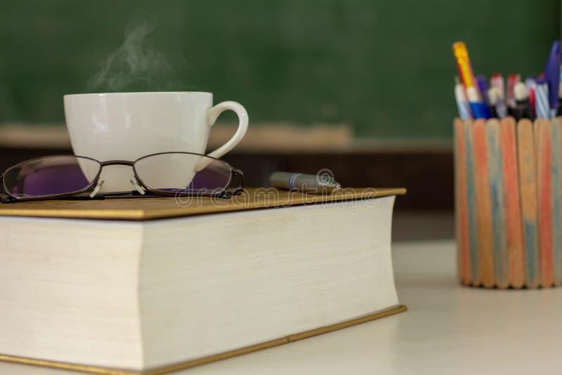 Koppen för vitt kaffe förläggas på boken fotografering för bildbyråer