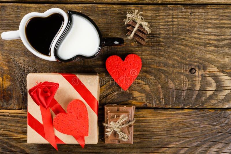 Koppen i formen av hjärtor, en hällde kaffe i annan mjölkar, den högg av chokladen tvinnar därefter bundet runt om den dekorativa royaltyfria foton