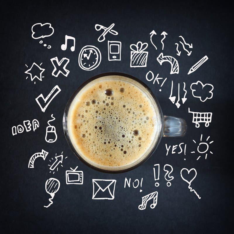 Koppen kaffe över svart tavla med skissar på bakgrund royaltyfria foton