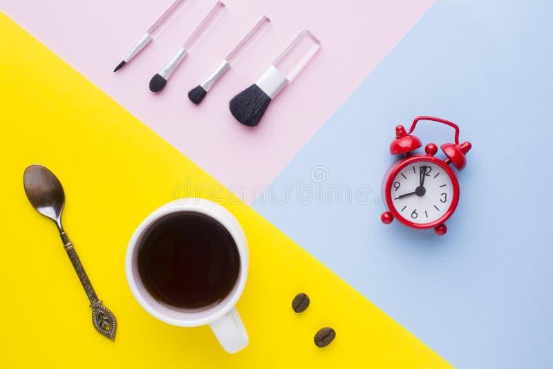 Koppen kaffe håller ögonen på klockan, och sminket borstar på färgrika bakgrunder Begreppsaffärsmorgon arkivbild