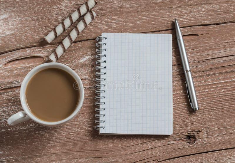 Koppen kaffe kex och förbigår den öppna anteckningsboken på en trätabell Top beskådar arkivbilder