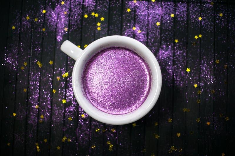 Koppen kaffe med lilor blänker på mörk bakgrund med guld- royaltyfria foton
