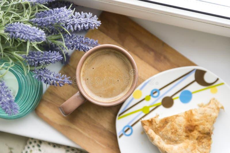 Koppen kaffe med mjölkar, ett stycke av kakan på en platta blå lavendelfilial arkivfoton