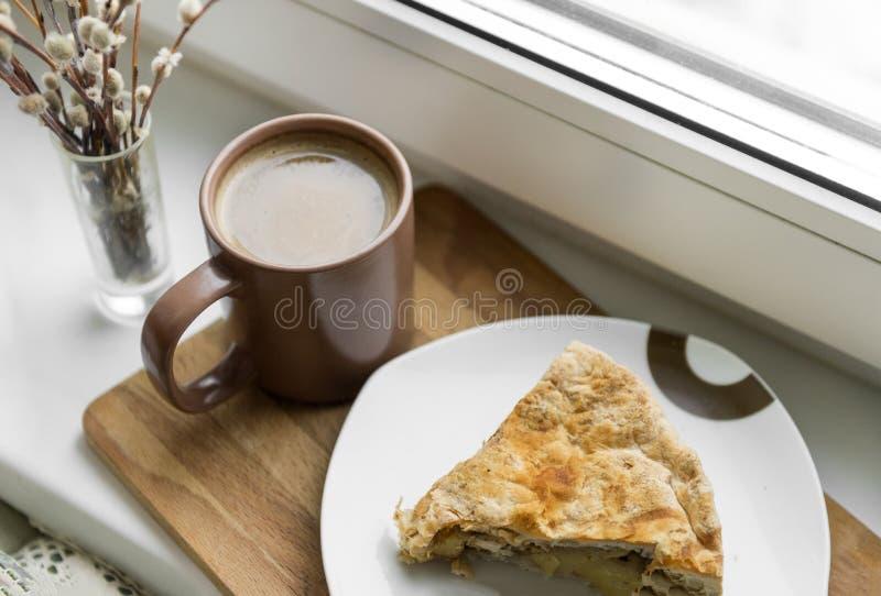 Koppen kaffe med mjölkar, ett stycke av kakan, pilfilial fotografering för bildbyråer