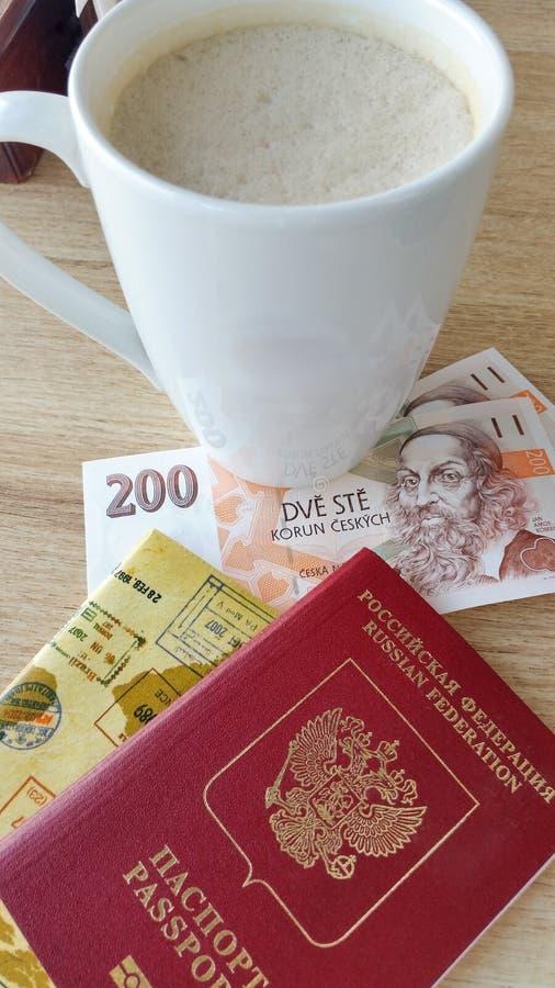 Koppen kaffe med mjölkar i flygplatskafé Pass och pengar på tabellen royaltyfri foto