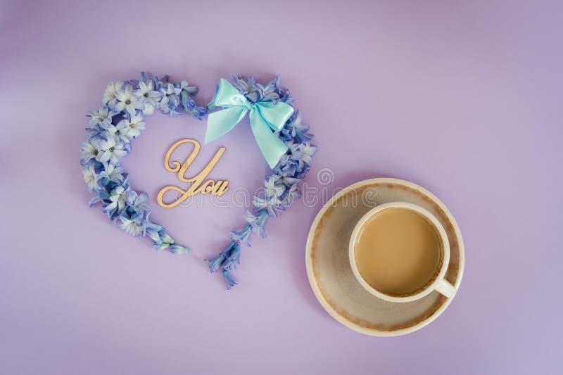 Koppen kaffe med mjölkar, och hjärta som göras från hyacint, blommar på purpurfärgad bakgrund arkivbild