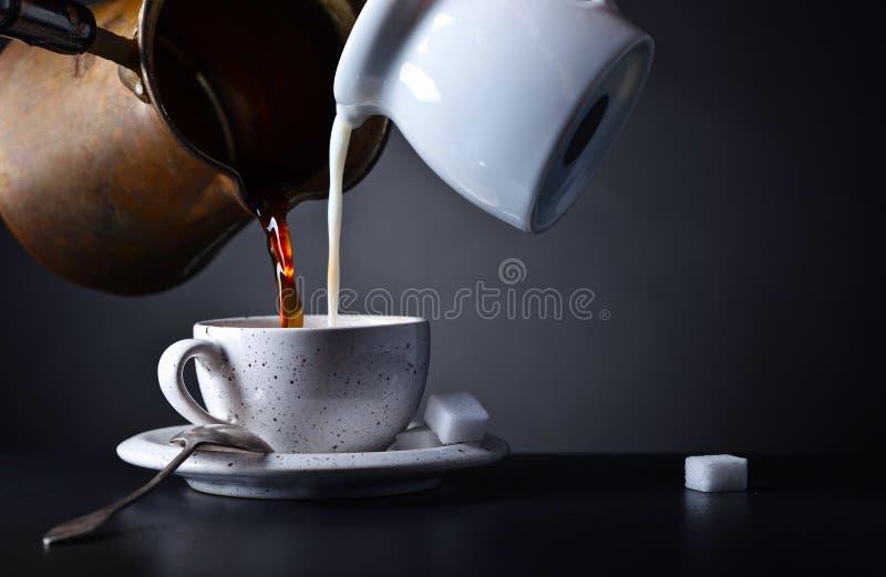 Koppen kaffe med mjölkar och sockrar på mörk bakgrund arkivfoton