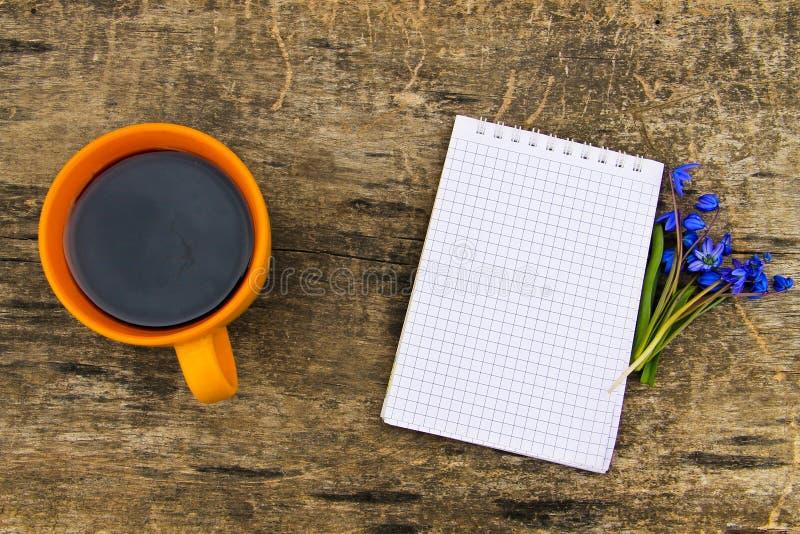 Koppen kaffe med notepad- och blåttscilla blommar på träskrivbordet arkivfoton