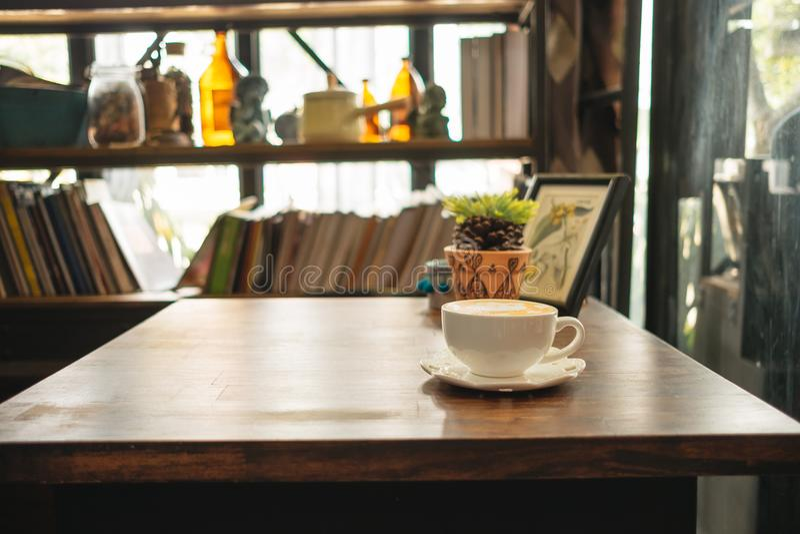 Koppen kaffe med växter och bildramen förlägger överst av trä royaltyfri foto