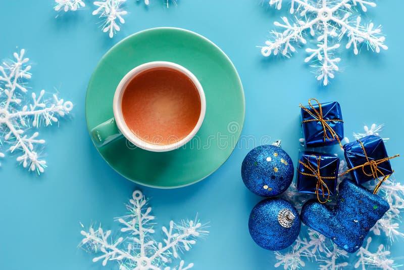 Koppen kaffe med Xmas-snöflingan, gåvaask, blänker bollar och b arkivbild
