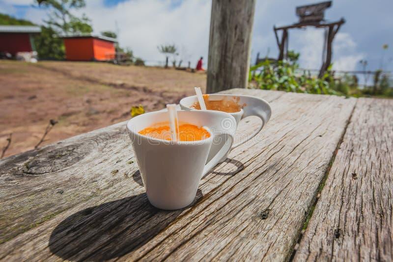 Koppen kaffe mjölkar te i trätabellbakgrund royaltyfri bild