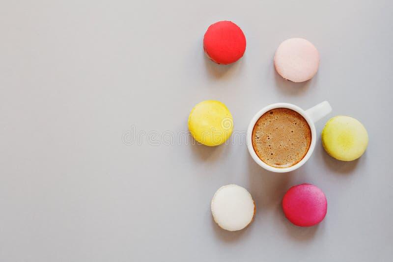 Koppen kaffe och blandade färgrika macarons eller makron på grå bakgrund, den bästa sikten, lägenhet lägger arkivbilder