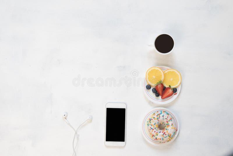 Koppen kaffe och munken med ostmassakräm dekorerade med smulor av röd frukt på vit bakgrund fotografering för bildbyråer