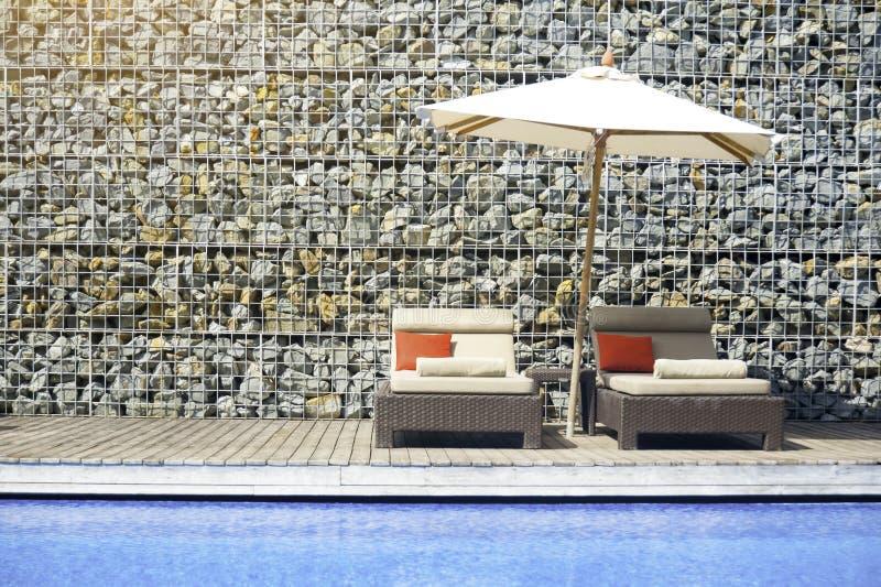 Koppla av atmosfär av simbassänghotellen med stenväggar som dekoreras i sommaren Stol som ska kopplas av vid hotellpöldäcket in fotografering för bildbyråer